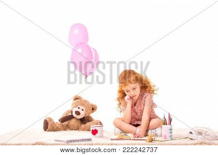 sad red hair kid sitting on carpet with pencil and notebook isolated on white