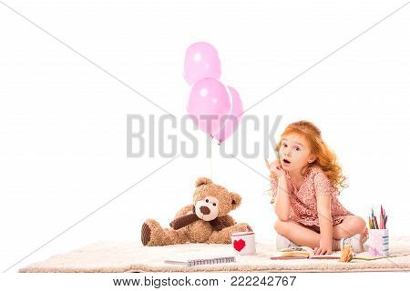 surprised red hair kid sitting with toys on carpet isolated on white