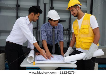 Engineering senior Asian manager and Young field engineer explain construction plan on paper to foreman at construction site. Business Teamwork success concept.