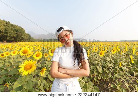 beauty asian woman stading in sunflowers field, traveling lifestyle
