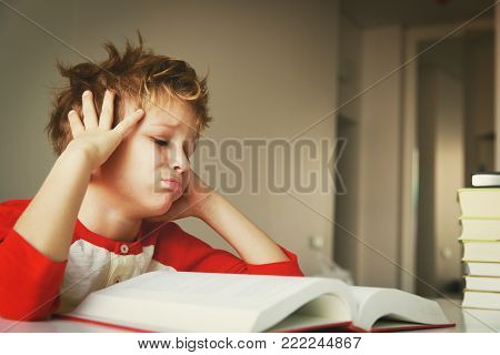 little boy tired stressed of reading, doing homework, learning