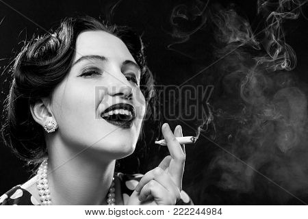 blond young woman smoking joint on black background, monochrome