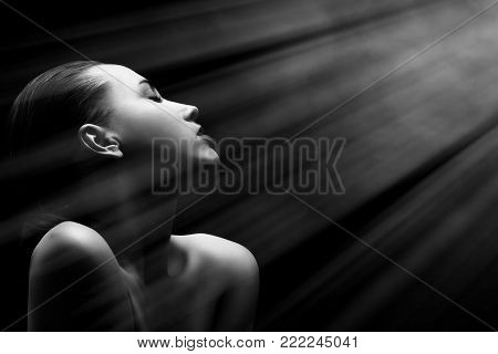 sensual aroused woman with closed eyes on black background with light rays, monochrome