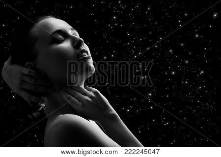 sensual aroused woman with closed eyes on stars background, monochrome