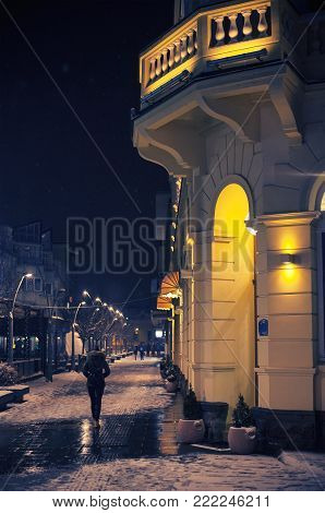 Night scene from the city promenade, entrance to the hotel with a certain passerby on the sidewalk, a winter period in Europe.