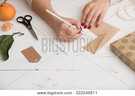 Close up of girl's hands writing a card for Christmas, birthday or any other celebration. Preparing present and card for celebration. Holidays season