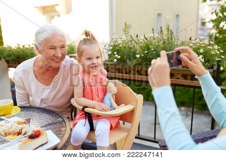 family, generation and people concept - happy smiling mother with smartphone photographing daughter and grandmother at cafe or restaurant terrace