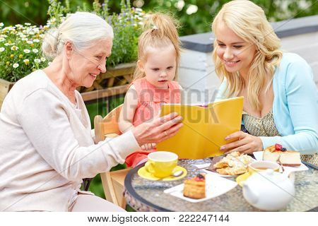 family, generation and people concept - happy mother with daughter and grandmother reading book at cafe or restaurant terrace