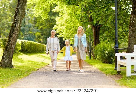 family, generation and people concept - happy smiling mother, daughter and grandmother walking at park