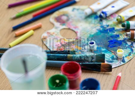 fine art, creativity and artistic tools concept - close up of palette, brushes, paint tubes and gouache colors on table