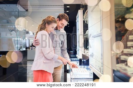 sale, consumerism, shopping and people concept - happy couple choosing engagement ring at jewelry store in mall