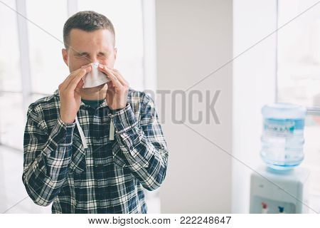 picture from a young man with handkerchief. Sick guy has runny nose. makes cure for the common cold