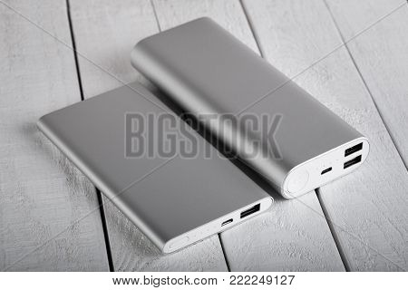 Battery Bank For Charging Mobile Devices. Silver Smart Phone Charger With Power Bank. External Batte
