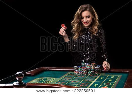 Sexy woman in a black dress playing in casino. Woman stakes piles of chips playing roulette at the casino club. Gambling. Roulette.