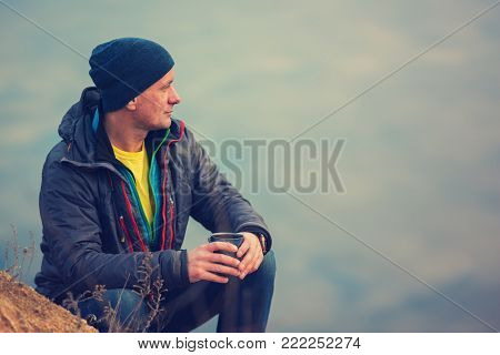 Thoughtful Traveler With A Mug Of Coffee Sits Near A Calm Lake