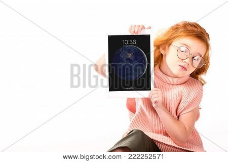red hair kid sitting and showing ipad tablet isolated on white