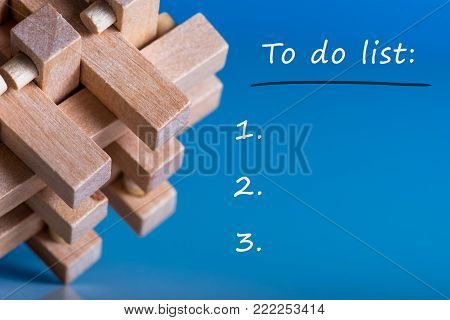 to do list at blue background with macro view of wooden brain teaser or puzzle.