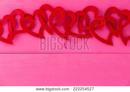 Red heart border for romance and love over a shocking pink background with copy space for your Valentines, wedding or anniversary greeting