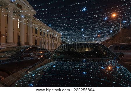 Part of a winter street lit by garlands, the light of which is reflected in parked cars