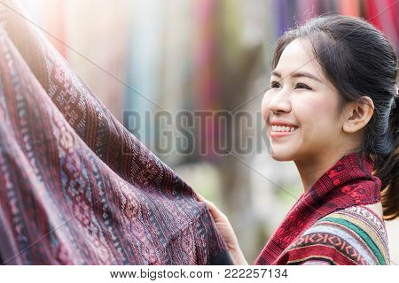 Happy asian traditional woman looking at Thai traditional fabric for dress making.