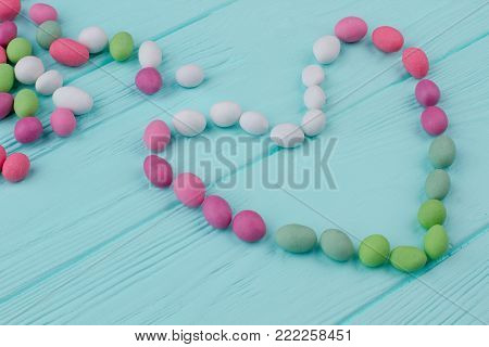 Colorful candies on wooden table. Form of heart from colorful candies. Love and romance. Valentines Day sweet composition.