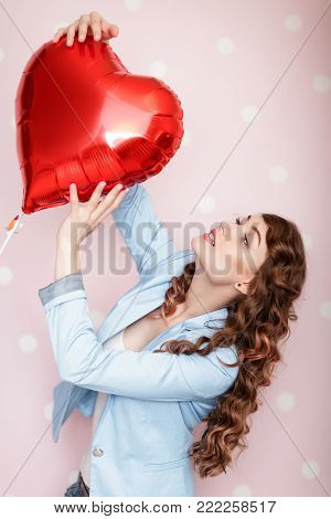 beautiful young curly woman catches heart shaped air balloons on pink background. St. Valentine's Day.