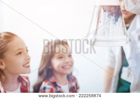 It is real magic. Scaled up shot of male scientist holding a flask with a liquid while little future chemists looking at the chemical reaction in the flask and grinning broadly.