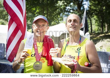 NEW YORK - JUL 16 2017: Achilles International athlete and guide relax after finishing the Panasonic New York City Triathlon Race in Central Park, the only International Distance triathlon in NYC.