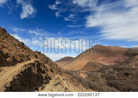 Atlas Mountains. Mountain panorama of walking hiking trail. Morocco, winter. Wild nature landscape. Village in the valley.