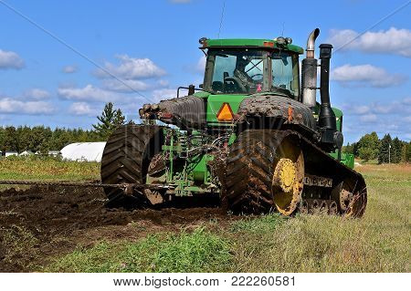 OSAGE, MINNESOTA, Sept 26, 2017: The 9620 T tractor maneuvering through mud is a product of John Deere Co, an American corporation that manufactures agricultural, construction, forestry equipment, machinery, and diesel engines,