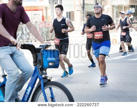 NEW YORK - JUL 16 2017: Athletes run by a bicyclist on West 72nd St during the 10k portion of the Panasonic New York City Triathlon Race, the only International Distance triathlon in NYC.