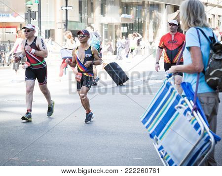 NEW YORK - JUL 16 2017: Athletes run by pedestrians on West 72nd St during the 10k portion of the Panasonic New York City Triathlon Race, the only International Distance triathlon in NYC.
