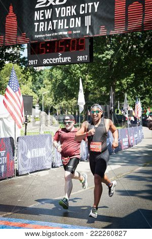 NEW YORK - JUL 16 2017: Athletes cross the finish line in Central Park of the Panasonic New York City Triathlon Race, the only International Distance triathlon in NYC.