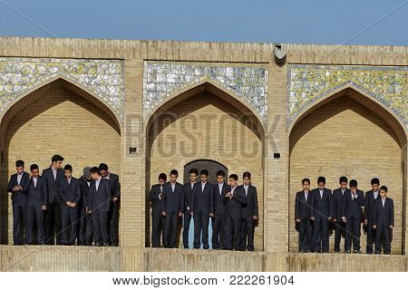 Isfahan, Iran - April 24, 2017: In niches of Khaju bridge are schoolboys dressed in strict suits, these students are participants of a children's choir that will sing for a television recording.