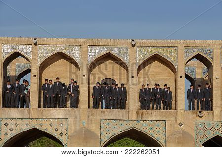 Isfahan, Iran - April 24, 2017: In the arched niches of the Khaju bridge there are boys in school uniform who will participate in a local festival as a children's choir.
