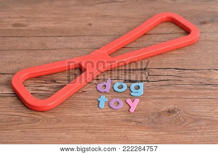 A red rubber tug of war toy for a dog with the word dog toy