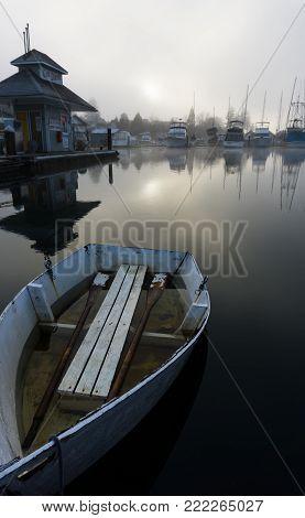 A single rowing boat on glassy-still water