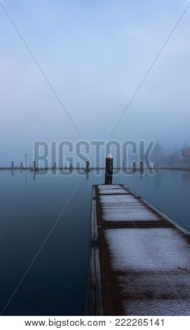 A portrait formatted view of an empty dock on a cold and misty morning.