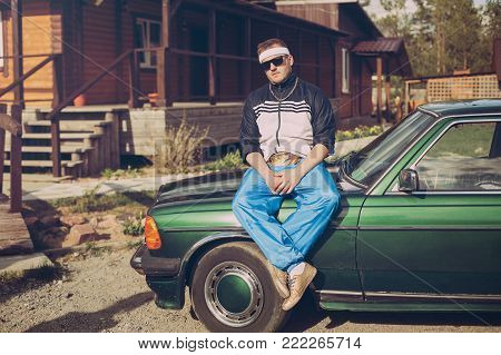 guy in the nineties sitting on the hood of the car in sunglasses