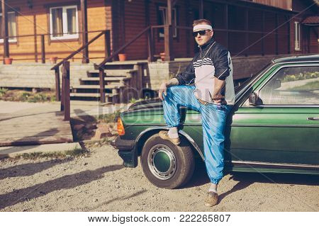 guy in the nineties stands near the car in sunglasses