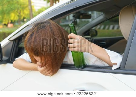 Drunk asian woman feels dizzy after too much drinking alcohol and driving car.