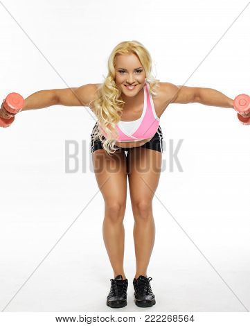 Cute blond fitness woman in colorful sportswear doing exercises with dumbells  on her back. Isolated on white background.