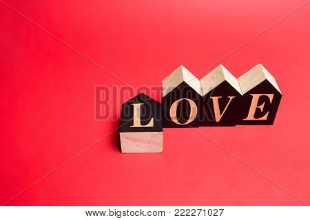 Love text on black wooden cubes on a red background