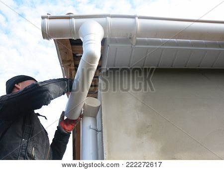 Roofer install and repair gutter system. Rain gutter installation with drain downspout pipe. Guttering.
