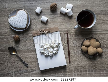 on a wooden background lies a craft notepad scrapbooking plate cookie heart pencil brown mug coffee marshmallow nuts lump paper mint spoon