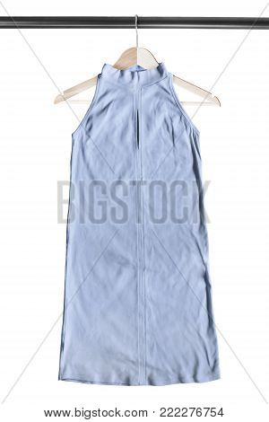 Blue halter mini dress hanging on wooden clothes rack isolated over white