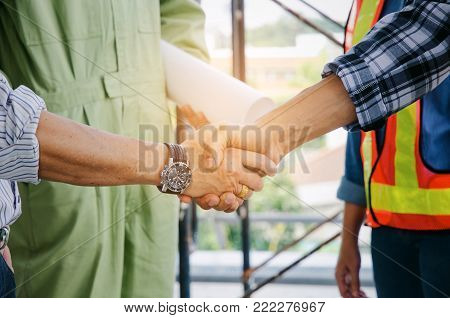 engineer and technician contractor shaking hands after finishing up a business meeting to greeting start up project contract in construction site building, successful, partnership, teamwork concept