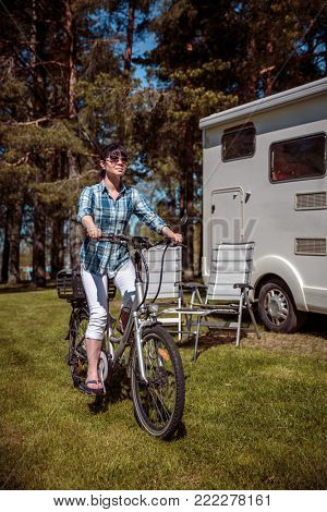 Woman on electric bike resting at the campsite. Family vacation travel, holiday trip in motorhome, VR Caravan car Vacation.