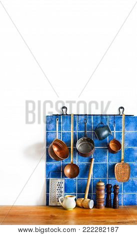Retro kitchen still life interior. Brass utensils, chef accessories. Hanging copper kitchenware set. Spoon, skimmer, grater. Blue tiles ceramic wall. spoon, pitchers, spices. White background copy space