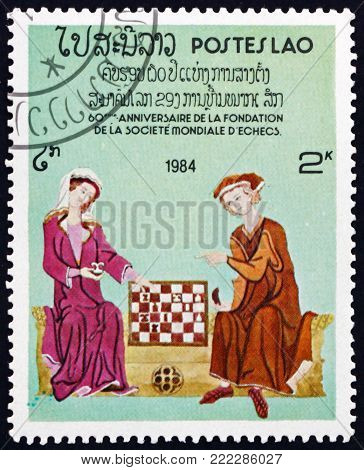 LAOS - CIRCA 1984: a stamp printed in Laos shows chess players, 60th anniversary of the World Chess Federation, circa 1984